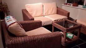 Lovely set of a two-seater rattan wicker sofa, two chairs and glass-top coffee table