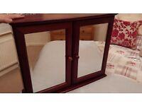 Teak bathroom cabinet with mirrored doors and glass shelves.