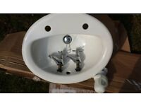 Large bathroom sink with taps and plug