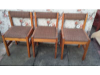 3 low wood framed chairs with padded seats and backs