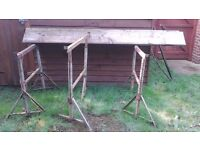 A SET OF THREE ADJUSTABLE TRESTLES WITH BOARDS