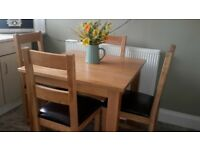 URGENT SALE SOLID OAK DINING TABLE WITH FOUR SOLID OAK CHAIRS.