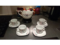 Teapot with a stand and 4 cups and plates