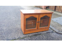 light brown wood tv unit with 2 glass doors at the front