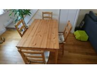 Dining table with four chairs and seat covers