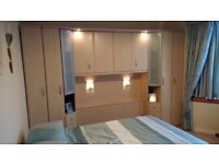 Over bed storage unit with cupboards.