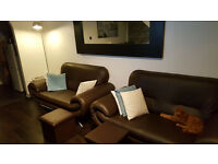 Brown faux leather sofa's.