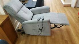 Grey fabric power recliner/riser chair with heated seat controlled with hand controllers
