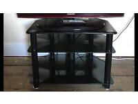 Black TV stand with pipe to hide cables