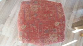 Fabric footstool with wooden carved legs