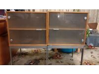 Two matching light wood shelved cabinets with glass fronts