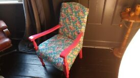 A vintage chair with wooden frame painted in pink and floral upholstery