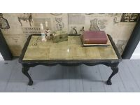 Vintage, stylish coffee table with old style music sheets and glass on the top.