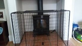 Black extendable fire guard. Minimum width 28 inches, maximum extension 50 inches. Depth 26 inches.