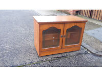 light brown wood tv cabinet with glass doors at the front