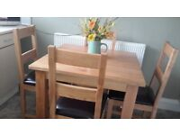 SOLID OAK DINING ROOM TABLE WITH FOUR SOLID OAK CHAIRS. IN LOVELY CONDITION.