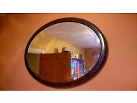 Early 20th century Art Deco oval stained oak bevel plate mirror.