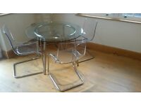 IKEA GLASS AND CHROME DINING TABLE WITH 4 PLASTIC AND CHROME CHAIRS