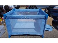 Light blue folding travel cot