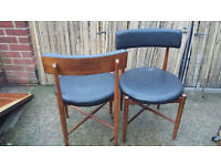 2 brown wood framed chairs with round black leather look seats