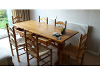 Pine dining table with 2 drawers. 6 matching chairs with woven wicker bases. All solid wood.