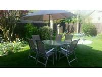 Glass table, 6 chairs and umbrella for sale