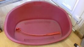 large red plastic dog bed and ball flinger