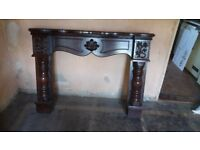Dark wooden fire surround and mantle in perfect order