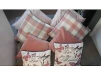 8 cushions in shades of pink and checked