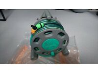 Garden hose reel, 15 to 20 m of new hose with end fittings.