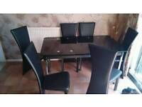 Extending black glass dining table with 6 high back chairs