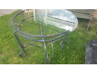 A round glass top wrought iron table in good condition