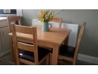 SOLID OAK DINING ROOM TABLE WITH FOUR SOLID OAK CHAIRS.
