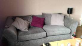 2&3 seater grey material sofas with light grey and purple cushions
