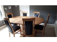 Solid oak extending round to oval dining table in excellent condition and 6 high back chairs