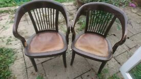 Two dark brown wooden chairs with leather seats