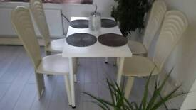 White table with 4 creme leather chairs