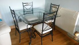Glass dining table with 4 grey and gold iron chairs