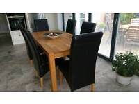 Sold oak table and six brown chairs