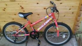 Child's bike new with helmet Red Raleigh 20 inch rims must be sold