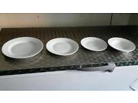 Various sizes of white plates and dishes