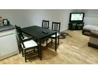 Table and 4 chairs with cushions in black fair condition