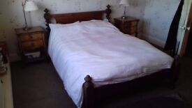 beautifulold mahogany double bed with scrolled headboard pillars.