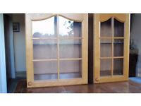 Two glass fronted display wall cabinets with oak door frame and glass shelf.
