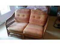 Two seater Cane settee . Ideal for conservatory or sunroom. Colour orange and red .