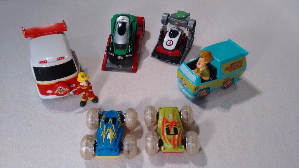 A variety of toy cars- Scooby-Doo trucks, two flip over stunt cars, and two race cars.