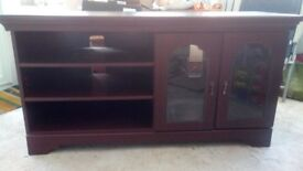 Mahogany coloured TV stand for sale. Two shelves and one glass fronted cupboard.