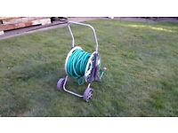 TENTY SEVEN METERS OF GARDEN HOSE ON A HOSE REEL IN GOOD WORKING ORDER.