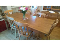 Solid pine dining table and matching chairs/cushions.