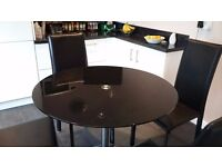 Black glass round dining table (seats four) with four black faux leather chairs